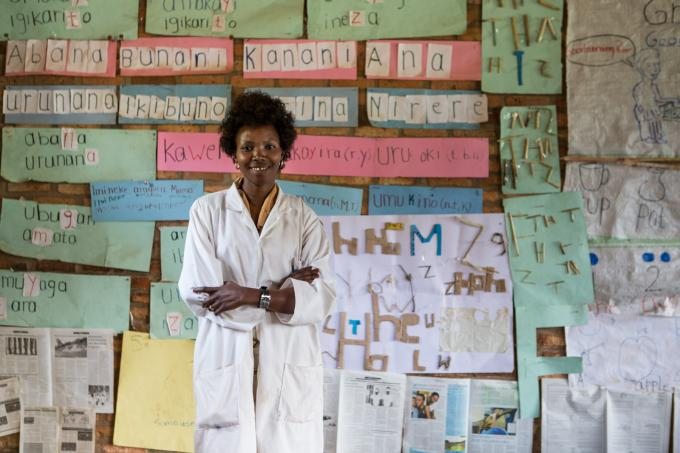 Grade 1 teacher poses in front of her classroom with many prints on the wall