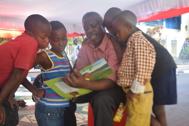 "A parent reading a story book to children during a ""read aloud session"" at the campaign launch"