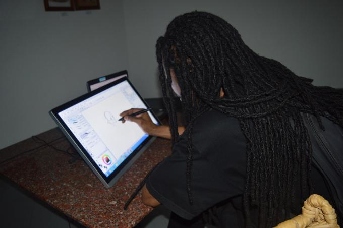 Seif Bizimana, one of the illustrators of Kinyarwanda children's books demonstrating a live illustration session during the website launch