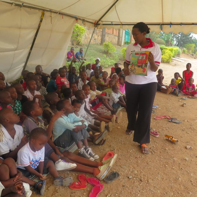 Caroline Dusabe, the Save the Children Early Childhood Development (ECD) Programme Manager   reads aloud a story-book to children