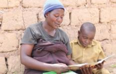 Mfitumukiza and his mother read together a storybook borrowed from the reading club